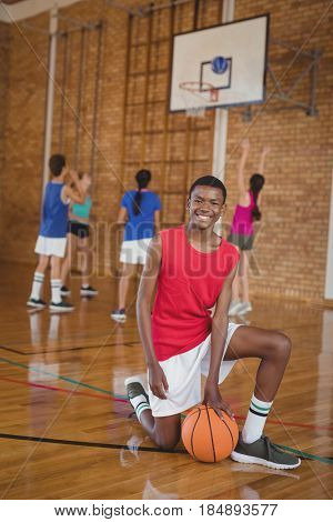 Portrait of smiling school boy kneeling with a basketball while team playing in background