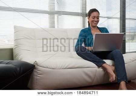 Hispanic woman on sofa using laptop