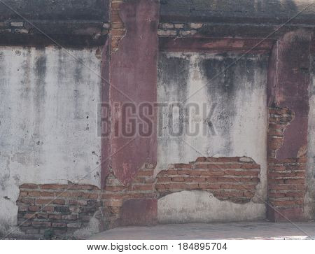 Old rendered wall with patches of exposed brick and stained with mold.