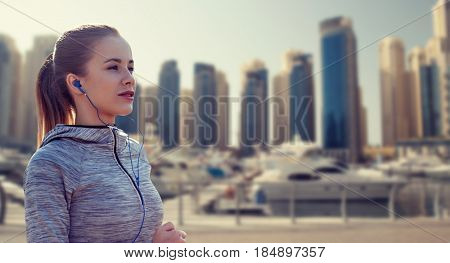 fitness, sport, people, technology and lifestyle concept - happy woman running and listening to music in earphones over dubai city street background