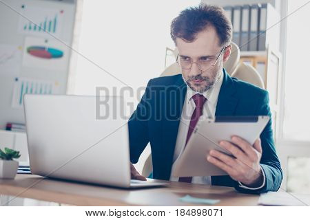 Serious Worker Is Typing Information From Tablet To Laptop. He Is In Formalclothes, Wearing Glasses,