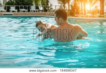 Father and son funny in  water pool under sun light at summer day. Leisure and swimming at holidays.