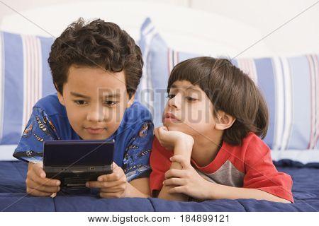 Hispanic boy watching brother using hand-held video game