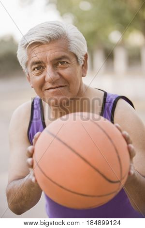 Senior Chilean man playing basketball