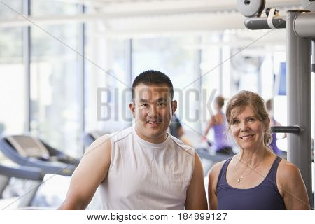 Woman standing with personal trainer in health club