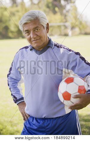 Senior Chilean soccer player holding soccer ball