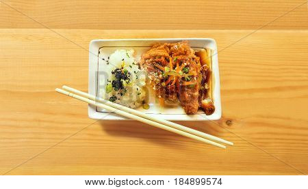 Sticky rice and fried chicken and bamboo chopstick Topping are sesame and carrot on top ceramic plate with bamboo chopstick On wood.