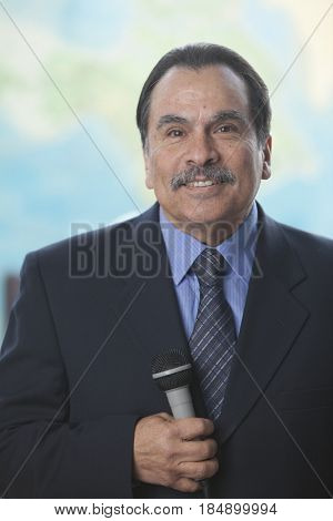 Smiling Hispanic businessman holding microphone