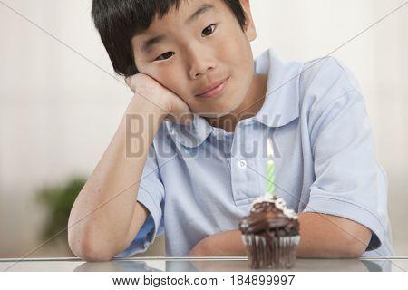 Smiling Korean boy looking at birthday cupcake