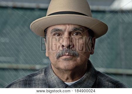 Serious Hispanic man wearing hat