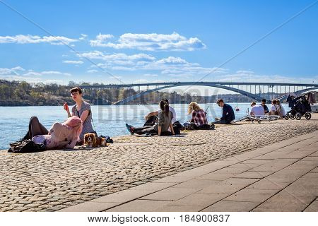 People relaxing on a quay. Stockholm, Sweden - May 01, 2017: Many young people sitting and laying on a quay in the center of Stockholm. Relaxing and sunbathing, water and bridge in the background.