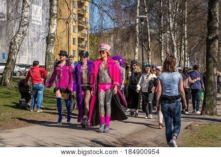 Dressed up people in a park. Stockholm, Sweden - May 01, 2017: Group of people walking in a park in central Stockholm. Showing off in colorful clothes and hats. Ordinary people passing by.