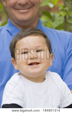 Chilean boy sitting on father's lap