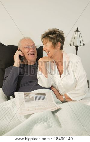 Senior Hispanic couple sitting in bed talking on telephone