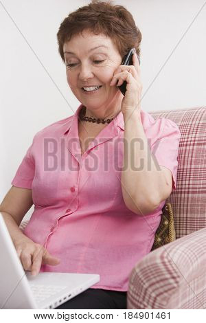 Senior Chilean woman using laptop and cell phone