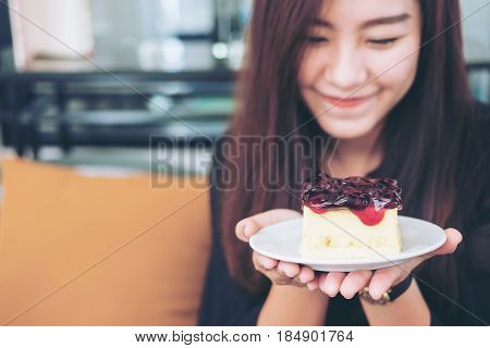 A beautiful asian woman holding blueberry cheese cake with feeling happy and good lifestyle in modern cafe