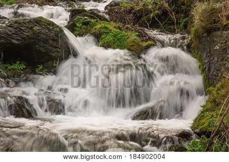 Small waterfall with fast rushing water on edge of Exmoor in North Devon England