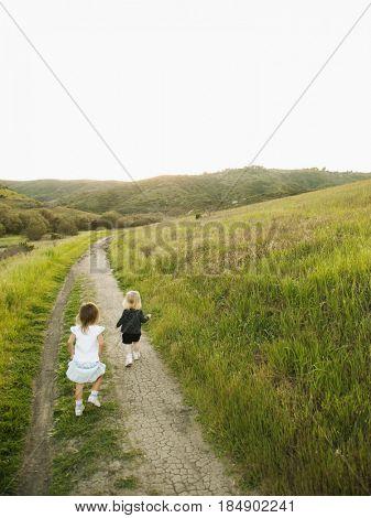 Girls walking on path in field