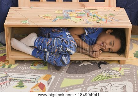 Hispanic boy hiding in chest