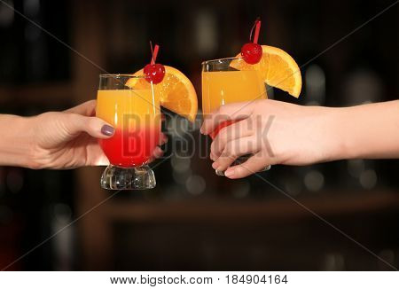 Women holding tequila sunrise cocktails