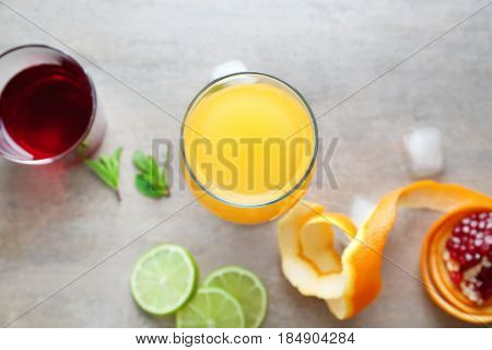 Glasses of Tequila Sunrise cocktail and ingredients on grey background