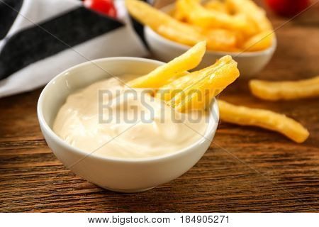 Bowl with tasty mayonnaise sauce and French fries on wooden table, closeup