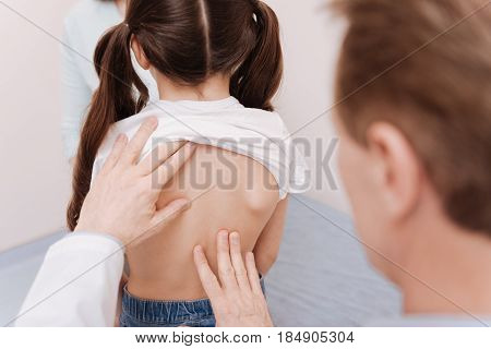Right posture development. Prominent polite local doctor running a checkup on little patients back and seeing no signs of problems