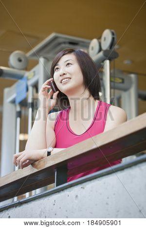 Korean woman talking on cell phone in health club