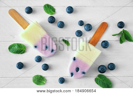 Homemade ice pops with blueberries on wooden background