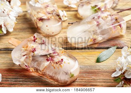 Homemade ice pops with flowers on wooden background