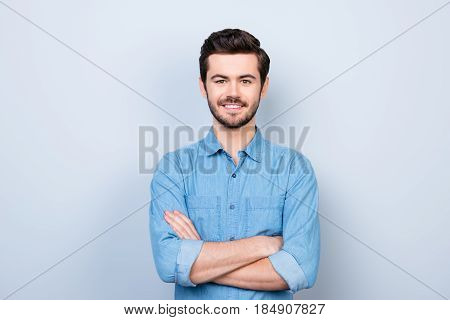 Close Up Portrait Of Cheerful Brunet Young Man In Jeans Shirt Crossing Hands And Look At Camera On L