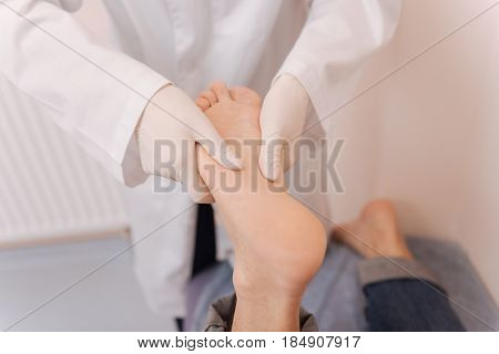 Making patient feel better. Good qualified young doctor wearing medical gloves for conducting a test on patient soles for diagnosing him