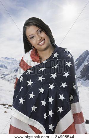 Hispanic woman wrapped in American flag