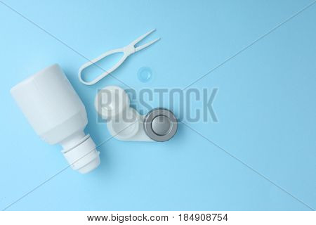 Case for contact lenses, tweezers and bottle of solution on blue background