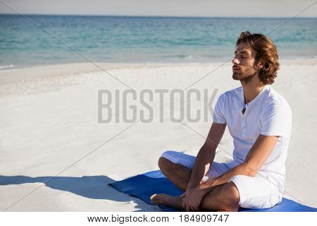 Man with eyes closed meditating while sitting on exercise mat at beach