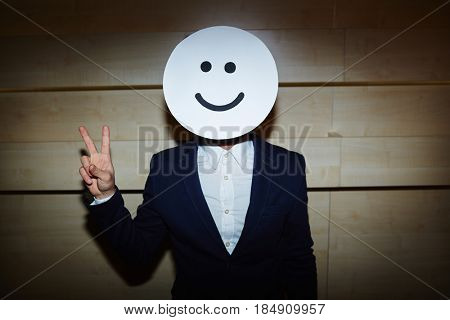 Waist-up portrait of successful entrepreneur in formalwear standing against wooden wall and showing V sign at camera, his face covered with smiling mask