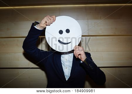 Unrecognizable man wearing suit posing for photography while covering his face with smiling mask, waist-up portrait