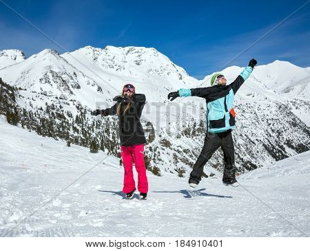 Happy couple jumping on the background of snowy mountains