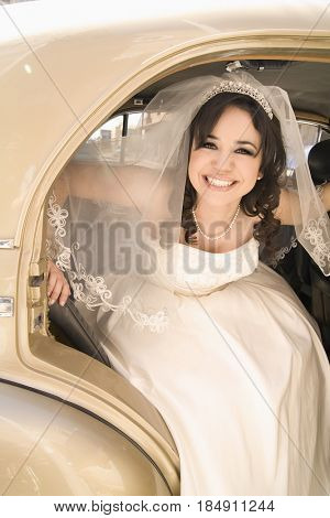 Hispanic bride getting out of car