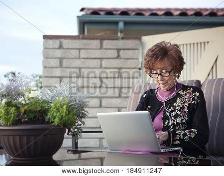 Senior Caucasian woman using laptop on patio