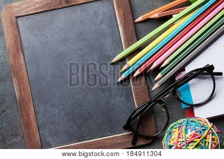 Chalk board for your text and supplies. Back to school concept with copy space