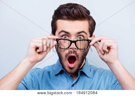 Wow! Really?! Surprised Young Handsome Man With Opened Mouth Touching Glasses