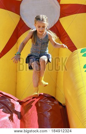 Joyful girl jumps on inflatable attractions in park