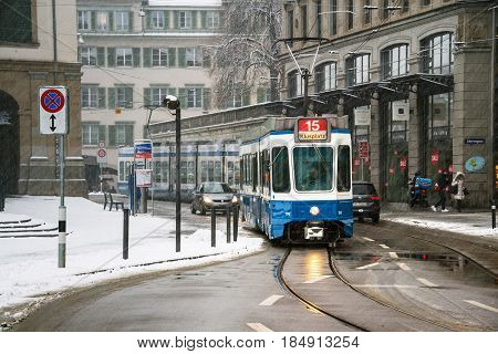 ZURICH, SWITZERLAND - JANUARY 10, 2017: Blue Tram in the city center of Zurich, Switzerland with local people. The system was electrified in 1890s and was developing since intro a huge network. Snow