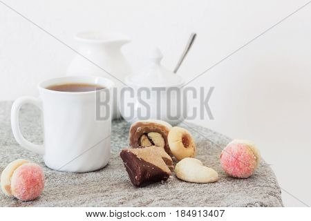 the cup of tea and cookies on table