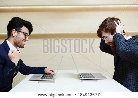 Cheerful entrepreneur sitting at one end of table and holding fist up while his colleague clutching head in despair and sitting at another end