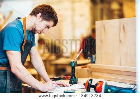 Portrait of focused young man working in carpenting studio, checking plans at workstation