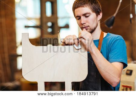Portrait of focused young man making furniture in carpenters workshop, sanding wooden detail with file