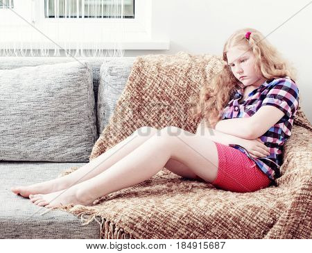 the child with stomach ache on sofa