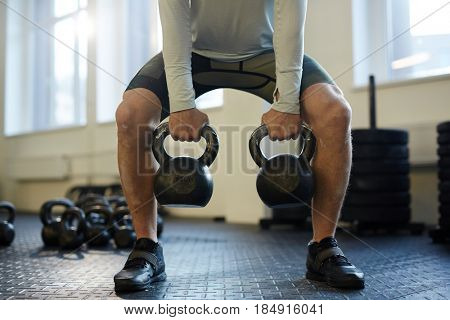 Low section portrait of unrecognizable man lifting two heavy kettlebells with vigorous effort during workout on gym